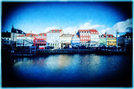 青色加工した川辺に佇む街並み